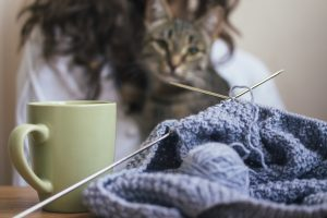 On the table is a knitting and a cup